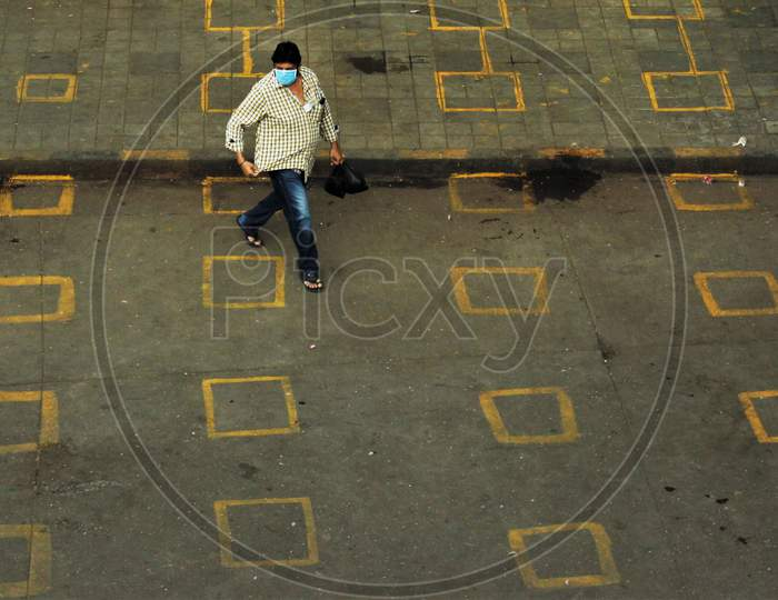 A man wearing protective mask walks on the squares painted by the BMC for maintaining physical distance at a market place to limit the spread of the coronavirus disease (COVID-19), in Mumbai, India on March 28, 2020.