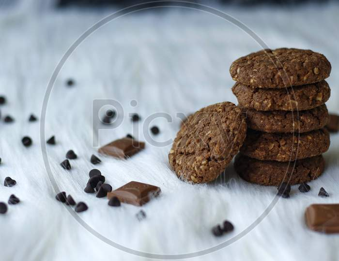Chocolate And Oats Cookies With Chocolate Chips And Chocolate Pieces On A White Fur Background