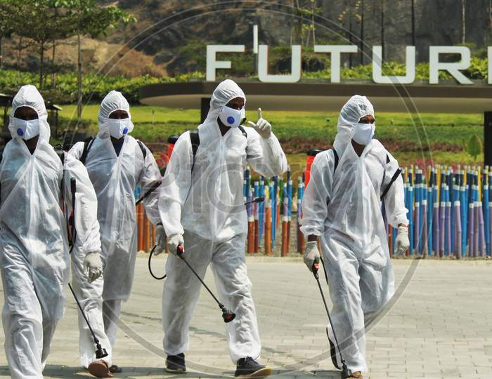 Workers wearing protective suits on their way to disinfect slum area and a temple as a preventive measure against the spread of coronavirus disease (COVID-19) in Mumbai, India on March 28, 2020.