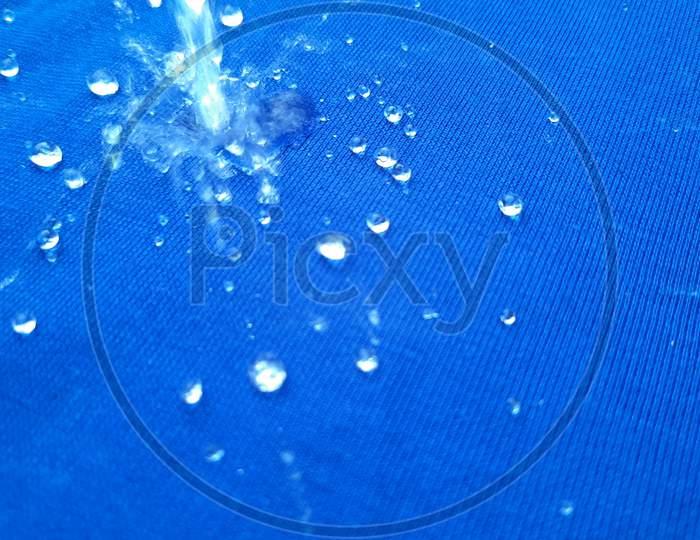 Rain Drop On Blue Surface ,Water Splash Like A Crown ,Water Splash In Crown Shape And Falling Drop