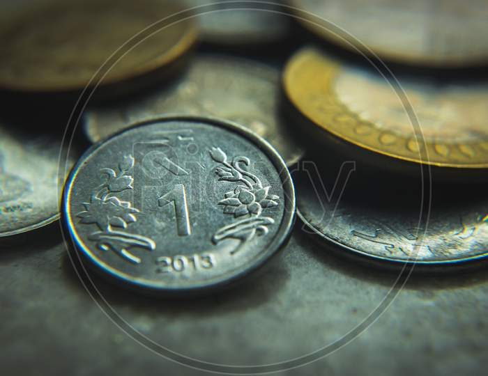Coins of Indian currency rupee (INR) . Golden five rupee , ten rupee coins and silver one rupee coins. Selective focus on coins with blurred background