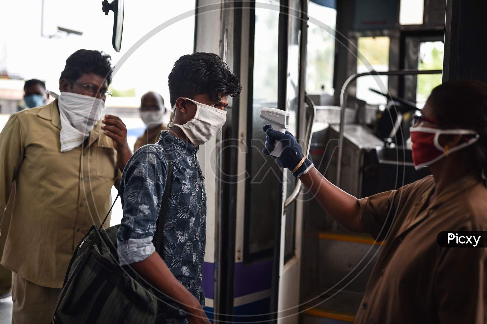An Apsrtc Worker Conducts Thermal Screening Of A Passenger Before Boarding A Bus, At Pandit Nehru Bus Station, During The Ongoing Coronavirus Lockdown, In Vijayawada.