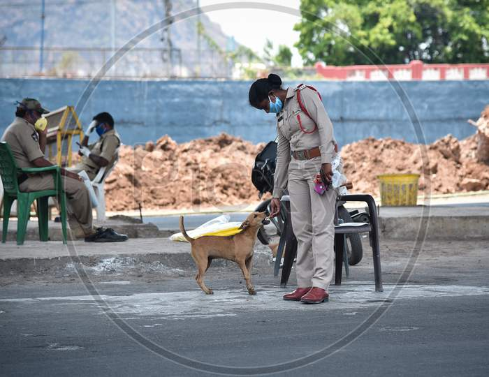 A Policewoman Feeds A Stray Dog During The Nationwide Lockdown Imposed In The Wake Of Coronavirus Pandemic, In Vijayawada.