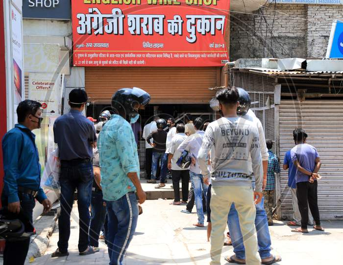 People stand in a queue to buy liquor outside a wine shop during an extended nationwide lockdown to slow the spread of the Coronavirus disease or COVID-19, in Prayagraj on May 4, 2020.