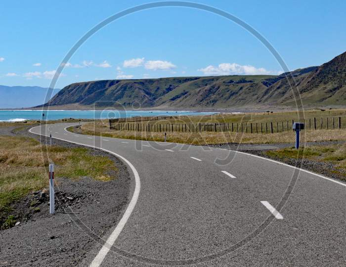 A Deserted Road Winds Towards The Bay At Cape Palliser, North, Island, New Zealand