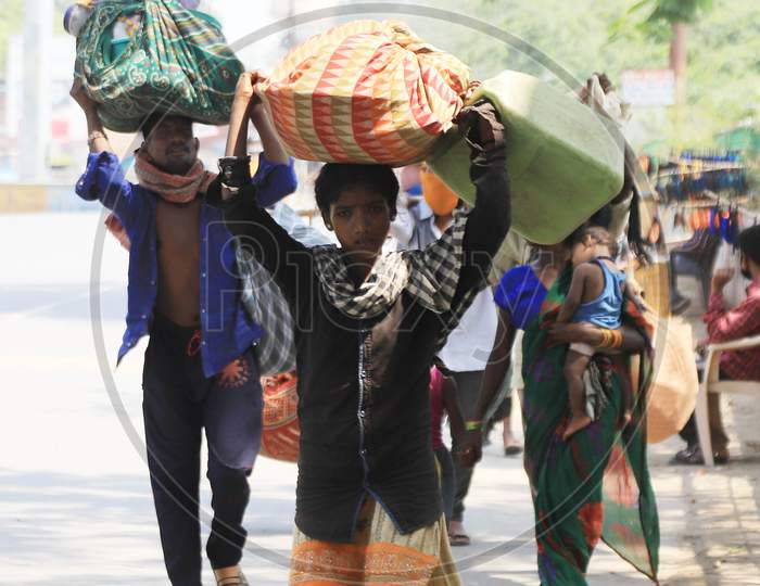 Migrant labourers carry goods as the walk on the road during an extended nationwide lockdown to slow the spread of the coronavirus disease, in Prayagraj, May 4, 2020.