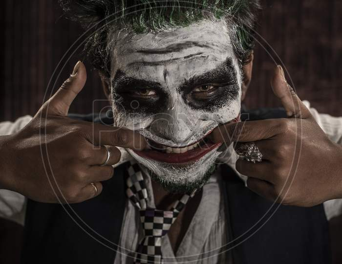 Portrait of an Indian man in Joker Halloween costume showing scary facial expression in front of a casino poker table. Cosplay photography.