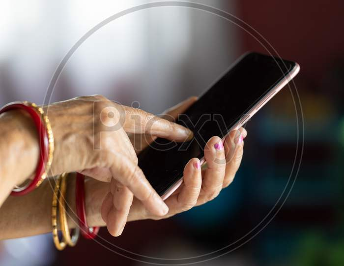 Closeup Shot Of Senior Woman'S Hand Holding Mobile Phone And Browsing