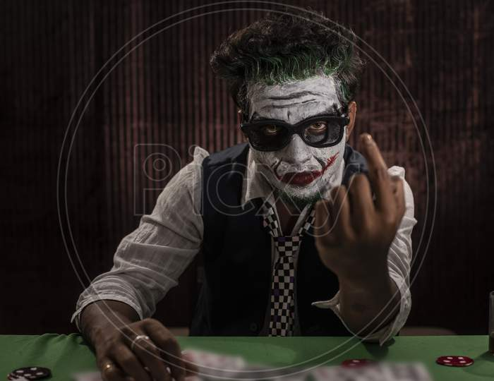 Portrait of an Indian man in Halloween Joker costume showing scary facial expression in front of a casino poker table. Cosplay photography.