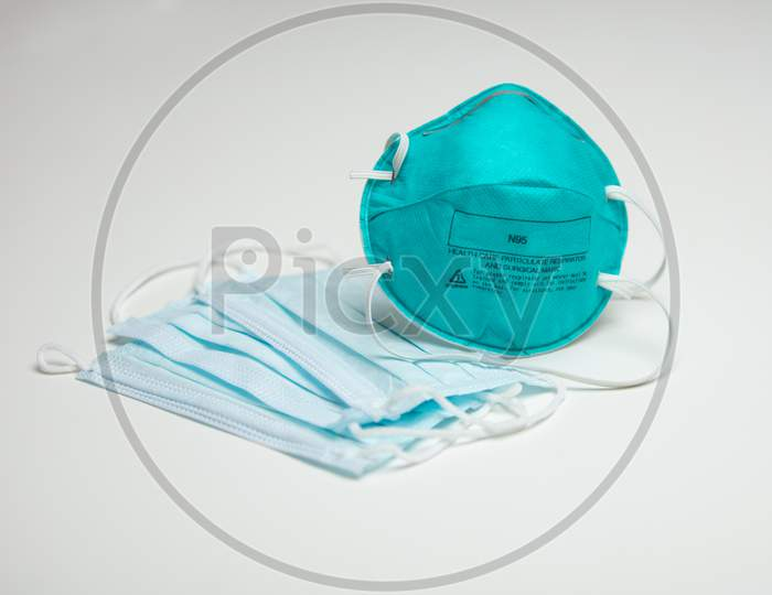 A Closeup Of An Assortment Of Protective Face Masks. One N95 And Three Surgical Masks.