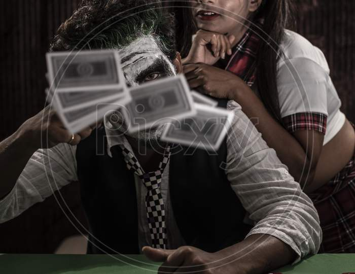 Portrait of an Indian couple in Halloween Joker costume playing cards in a casino poker table in textured studio background. Cosplay photography.