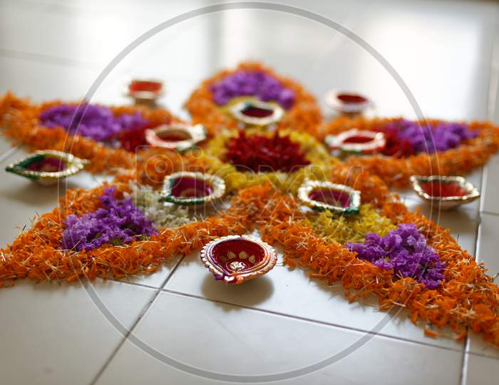 Beautiful holy rangoli is prepared by vibrant colorful flowers and decorative colorful diyas/lamps in white floor. Indian lifestyle and Diwali celebration.