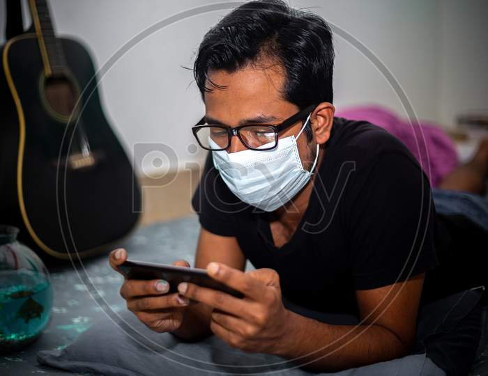 Bangladesh – April 14, 2020: A Surgical Mask-Wearing Young Man Was Playing Mobile Games On His Own Home Due To Coronavirus Home-Quarantine At Dhaka.