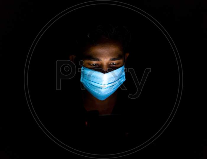 Bangladesh – April 14, 2020: A Blue Surgical Mask-Wearing Young Man Was Playing Mobile Games At Dhaka.