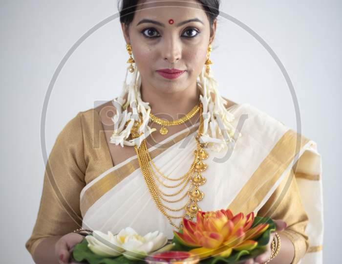Portrait of an young and attractive Indian woman in white traditional wear with colorful flowers in hands for the celebration of Onam/Pongal in white background. Indian lifestyle