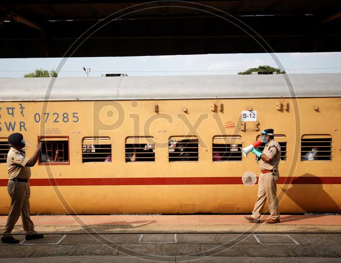 A Railway Protection Force (RPF) personnel uses a megaphone to make a public safety announcement to people travelling to Danapur, Bihar in a special train arranged by the government to repatriate migrant workers at the Chikkabanavara Junction Railway Station on the outskirts of Bangalore, India.