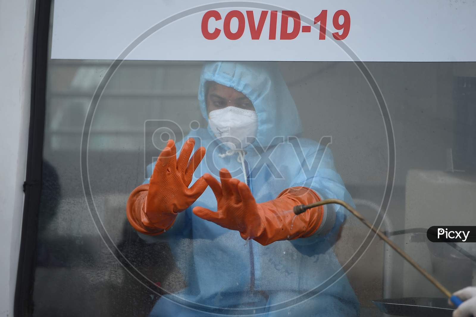 Medics Wearing Protective Suits Sanitise Their Hands After they Collect Swab Samples For Labourers Of Koyambedu Vegetable Market During A Government-Imposed Nationwide Lockdown As A Preventive Measure Against The Spread Of Covid-19 Or Coronavirus, In Chennai