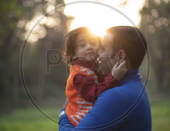 An Indian Telugu brunette father and his baby boy in winter garments enjoying themselves in winter afternoon on a  green grass field in forest background. Indian lifestyle and back light photography.