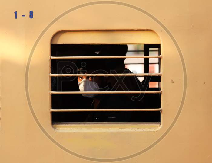 A man looks out of the window as he travels to Danapur, Bihar in a special train arranged by the government to repatriate migrant workers at the Chikkabanavara Junction Railway Station on the outskirts of Bangalore, India.