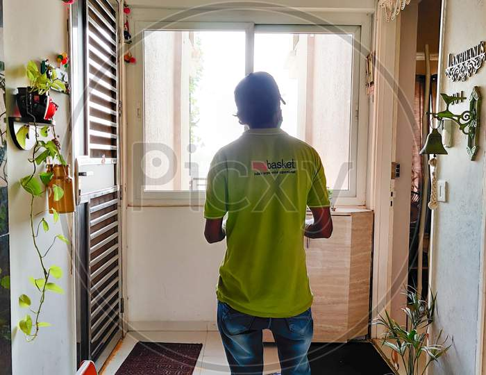 Delivery Boy From Big Basket Standing At Door Step Of Apartment To Deliver Grocery