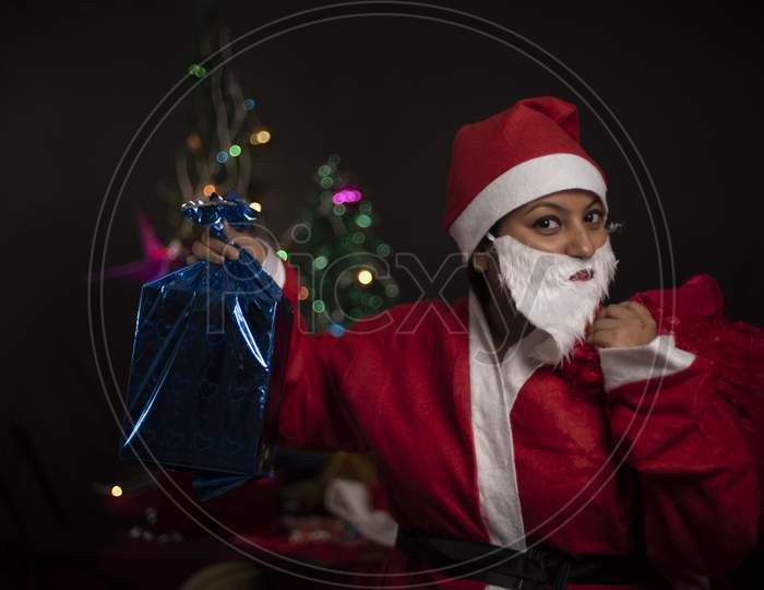 Young Indian plus size brunette woman in Santa Clause jacket and hat carrying her red bag in a funny and happy mood in decorative Christmas tree background. Indian lifestyle and Christmas celebration.