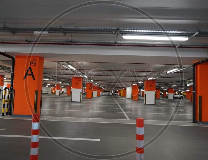Dubai Uae December 2019 Underground Parking Which Is Almost Empty. Empty Garage In Basement Of Office Building. Reinforced Concrete Monolithic Floors In Basement. Urban, Industrial Background.