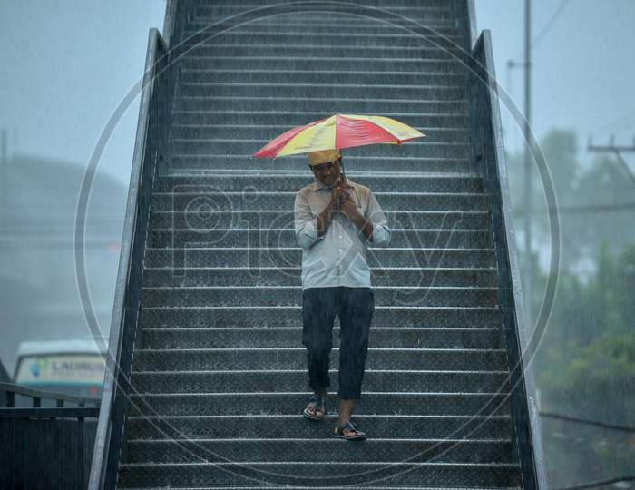 a man walks with an umbrella as it rains heavily in KPHB, Hyderabad, May 31, 2020.