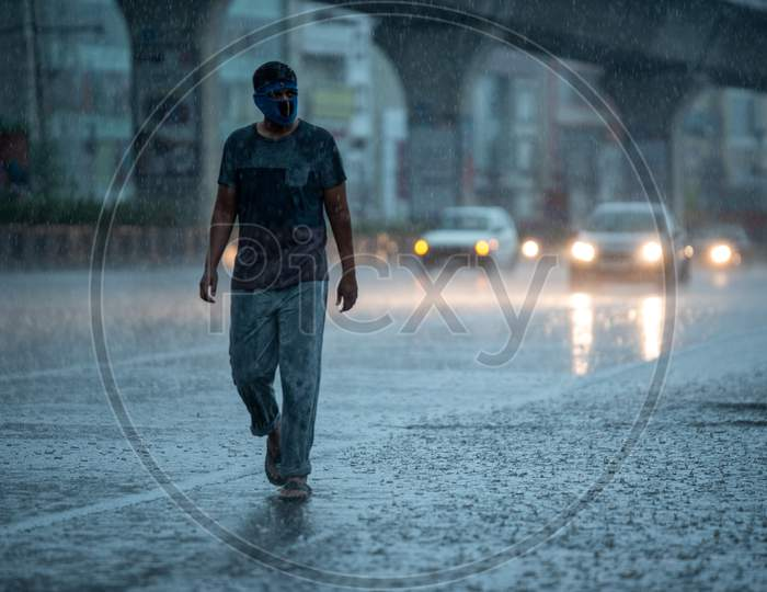 a masked man walks on the road as it rains heavily during the nationwide lockdown amid fears of coronavirus, may 31, 2020, Hyderabad