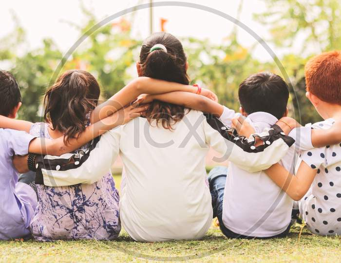 Back View, Group Of Kindergarten Multi Ethnic Kids Friends Arm Around Sitting Together At Park Outdoor - Concept Showing Of Childhood Friendship, Togetherness With Diversities.