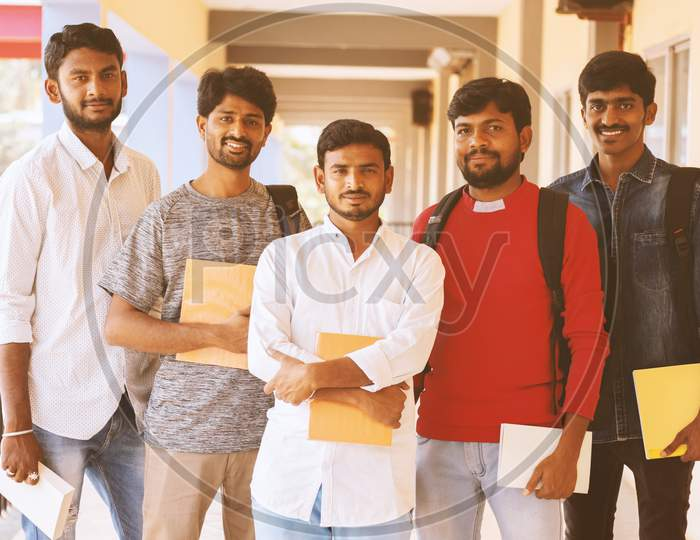 Happy Young Students Holding Books And Standing At College Corridor - Group Of Multiracial Confident Youth At University Campus - Concept Of Friendship, Togetherness And Student Life.