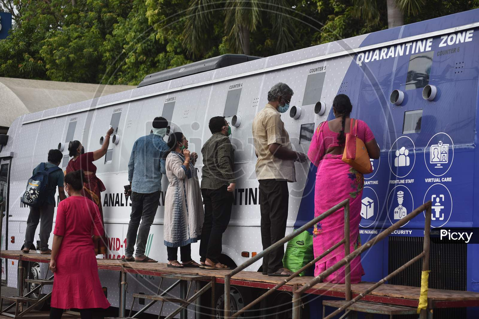 Passengers wait at a mobile swab collection bus, after their arrival at Vijayawada by Konark Express train, from amobile swab collection bus, atVijayawada Railway Station.