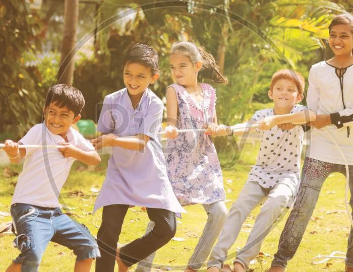Group Of Multi Racial Children Playing Tug Of War Game Kindergarten - Multi Ethnic Kids Playing Outdoor Games Against Racism.