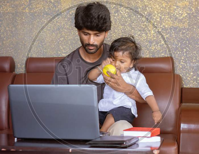 Young Father With His Little Son Working On Laptop At Home - Concept Of Work Form Home Or Wfh Reality, People Lifestyles And Technology
