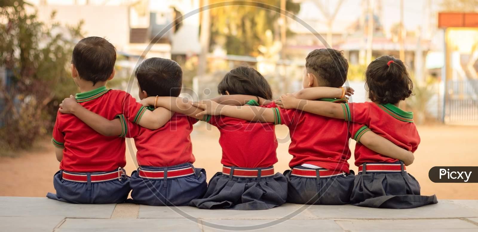 Back View, Group Of Kindergarten Kids Friends Arm Around Sitting Together