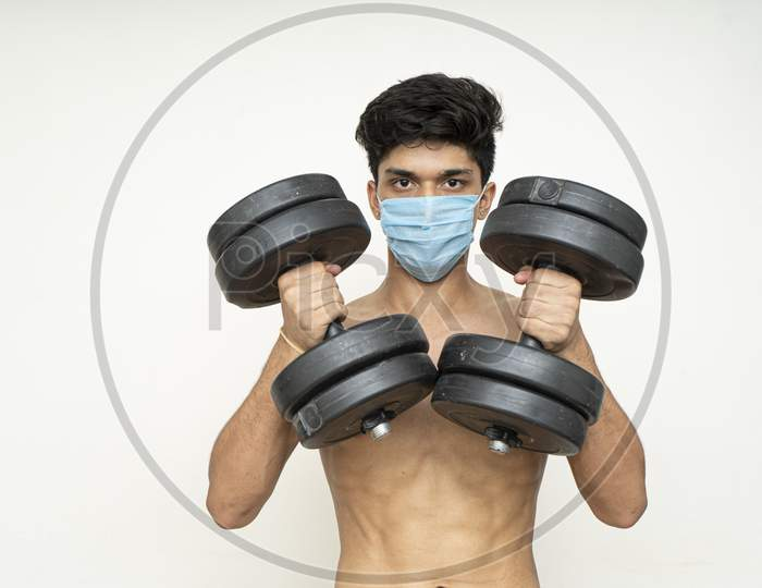 Fitness Man With Mask For Epidemic Protection Working Exercise For Arm,Biceps, And Shoulders With Dumbbells.Training In Epidemic Time
