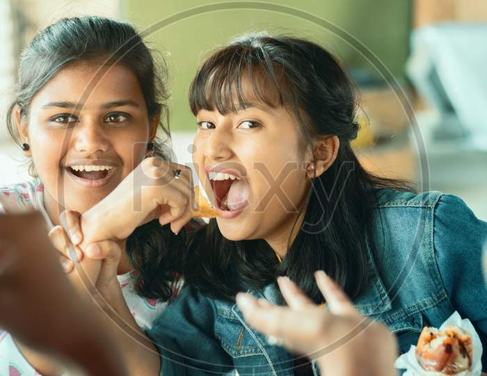Teenager Trying To Take Or Grab Food From Friend - Young Girl Playfully Fighting For Snacks With Her Friend - Concept Of Friends Having Fun While Having Food At College Restaurant.