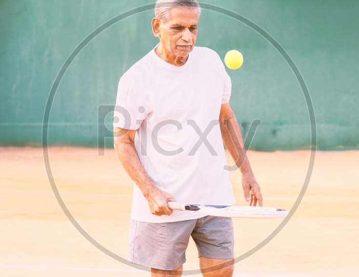 Elderly Man Playing Tennis - Concept Of Healthy And Fit Old People - Senior Player Practicing Tennis.