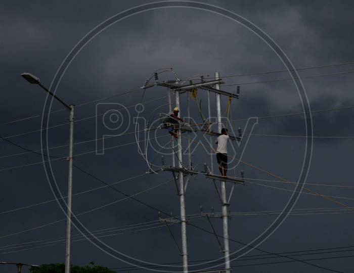 Labourers Work On An Electric Pole As Dark Clouds Cover Over The Sky, In Guwahati On Saturday, June 13, 2020.
