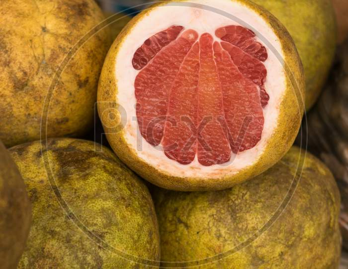 Ripped Pomelo Fruit Displayed In A Local Fruit Shop. One Is Peeled From The Front Side