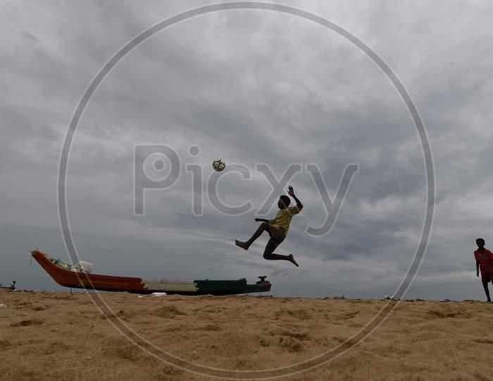 A Boy Plays Football On A Cloudy Day AtMarinaBeach,Chennai