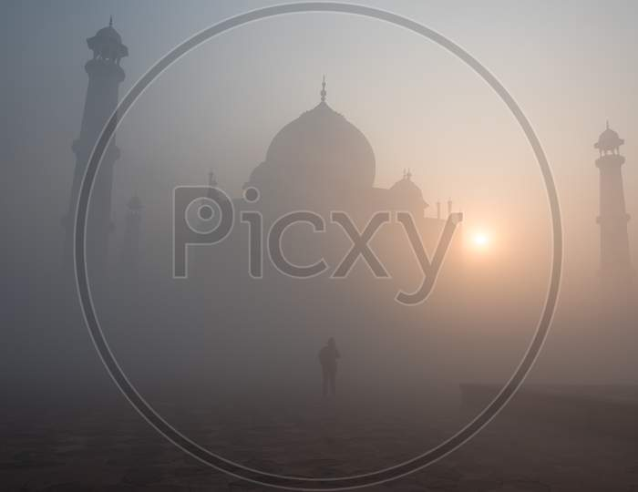 A lone admirer at the Taj Mahal on a early foggy winter morning.
