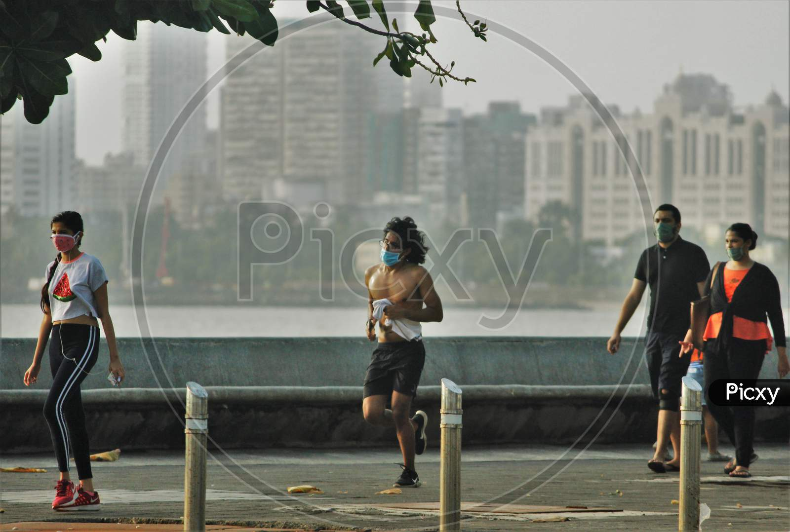 People walk and jog along the promenade at Marine Drive after some restrictions were lifted in Mumbai, India, June 6, 2020.