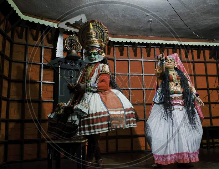 Kochi, India - March 15, 2014: An Indian Classical Dance Form Named Kathakali Artists Tells Indian Mythological Stories Through Numerous Gestures Techniques And Emotions In Front Of European Tourists.