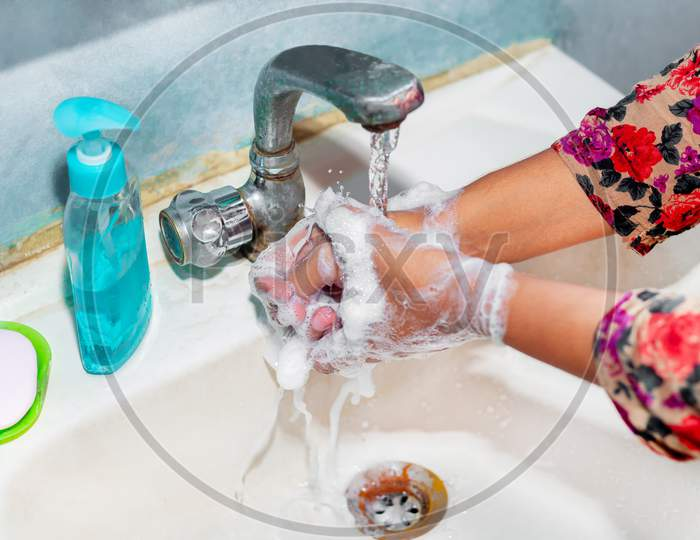 Women Use Liquid Soap For Rubbing And Washing Her Hands Under The Water Tap. Hygiene Concept. Wash Hands To Stop Spreading Coronavirus.