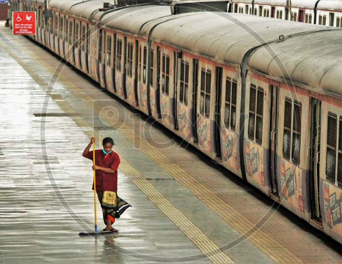A railway worker sweeps the platform on the first day of local trains resuming for essential service workers after the government eased a nationwide lockdown which was imposed as a preventive measure against the COVID-19 coronavirus, at CST local train station, in Mumbai, India, on June 15, 202
