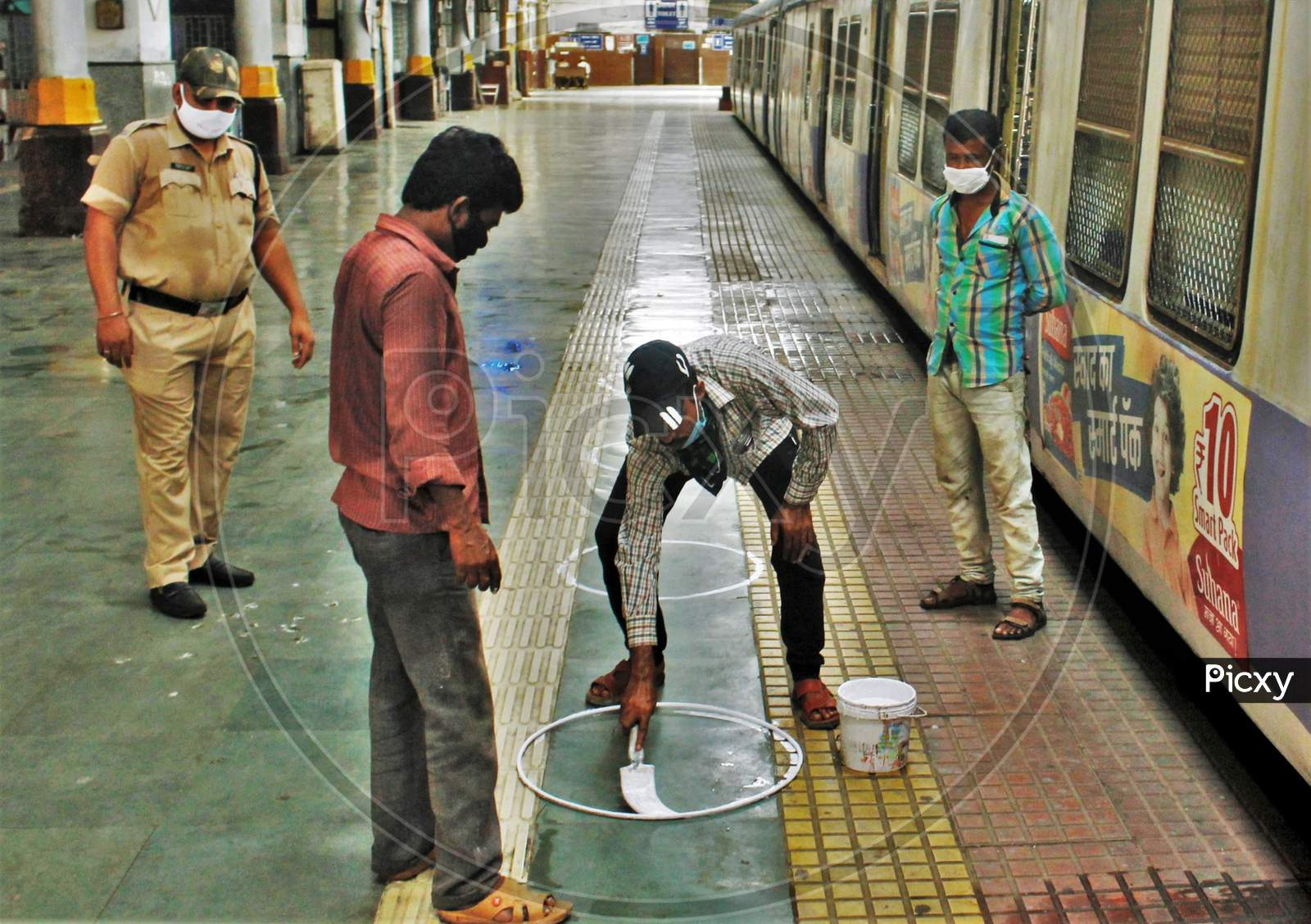Workers Paint Circles On The Platform For The Passengers To Maintain Social Distancing After The Government Eased A Nationwide Lockdown Which Was Imposed As A Preventive Measure Against The Covid-19 Coronavirus, At The Cst Local Train Station, In Mumbai, India, On June 15, 2020.