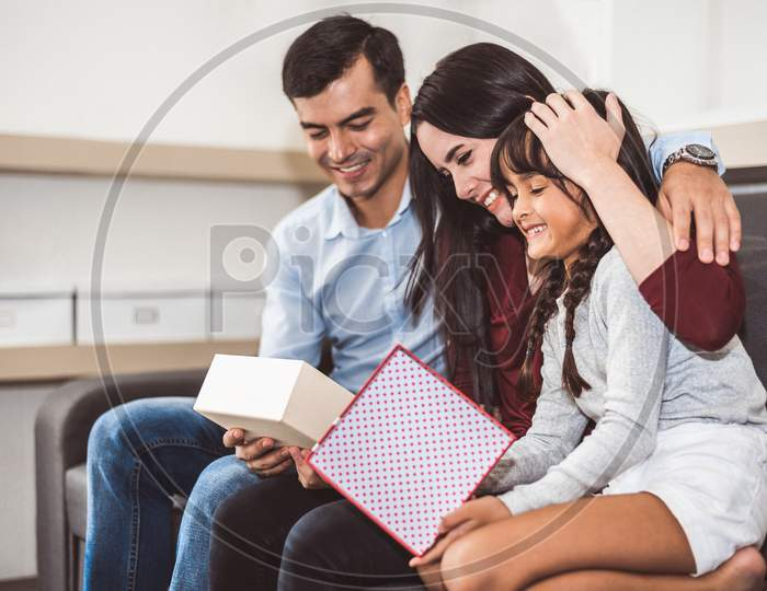 Happy Family Parents And Little Girl Looking Into Gift Box In Christmas And New Year Day On Sofa In Living Room. Xmas Present For Surprised Good Children In Happy Home. People And Lifestyles Concept.