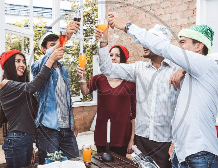 Outdoor Xmas Party Shot Of Young People Toasting Drinking Glass At A Rooftop Terrace As Forever Friendship. Young Friends Hang Out With Alcohol Drinking And Juice. Christmas And New Year Party Theme.