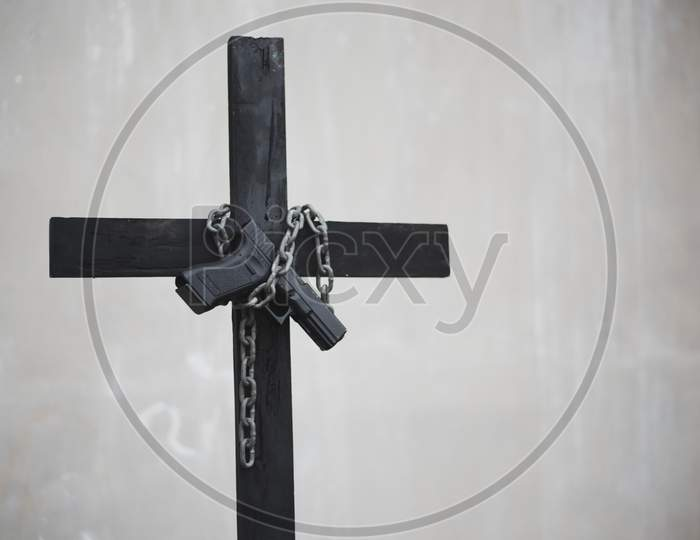 Black Cross With Chain And Handgun On White Grunge Wall. Object And Weapon Concept. Christian Religion Theme. Halloween And Criminal Theme. Copy Space On Right.