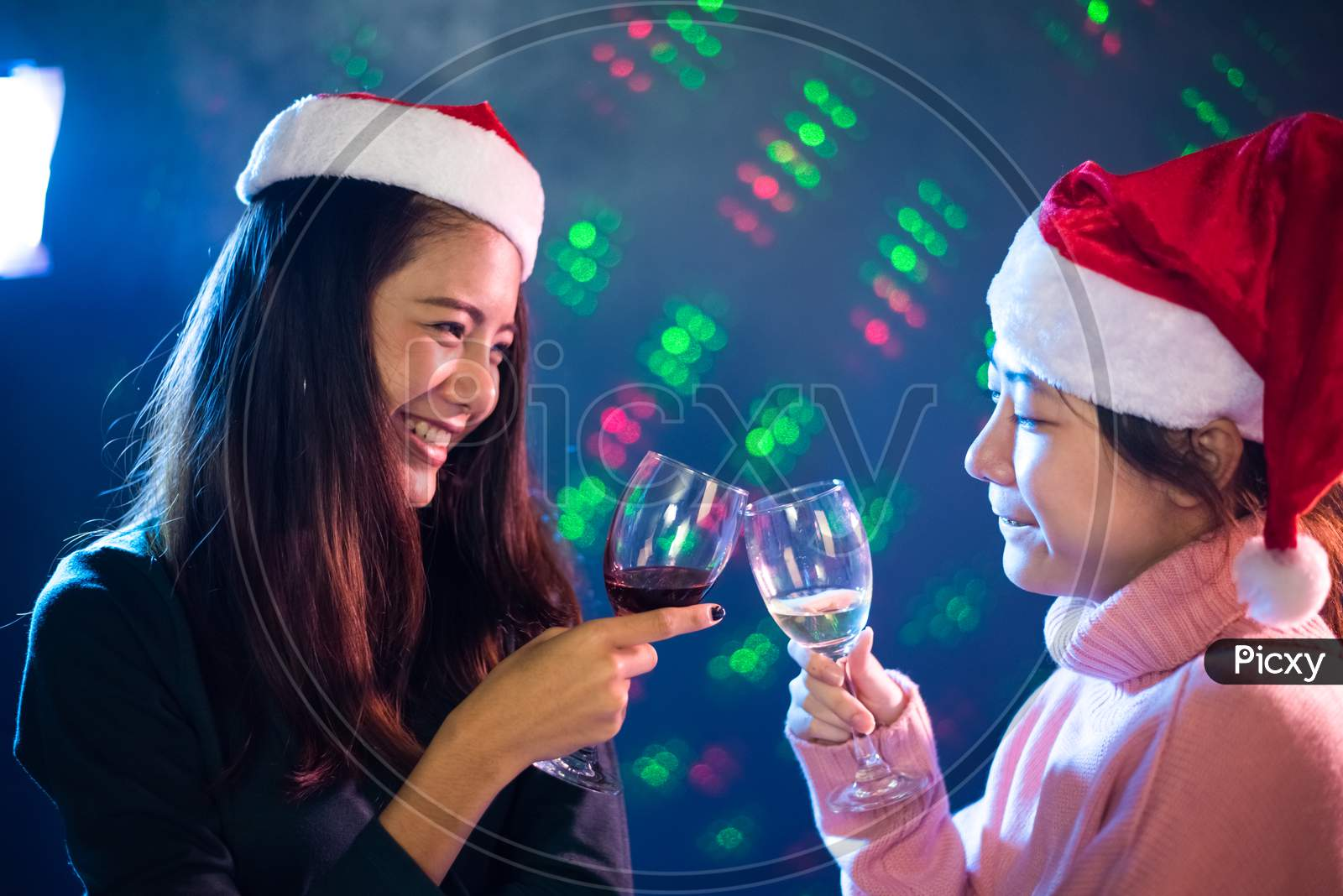Two Asian Woman Celebrating Christmas And New Year Party With Toasting Wine Glasses In Pub. People And Night Life Concept. Party And Event Theme. Clink Glasses Together